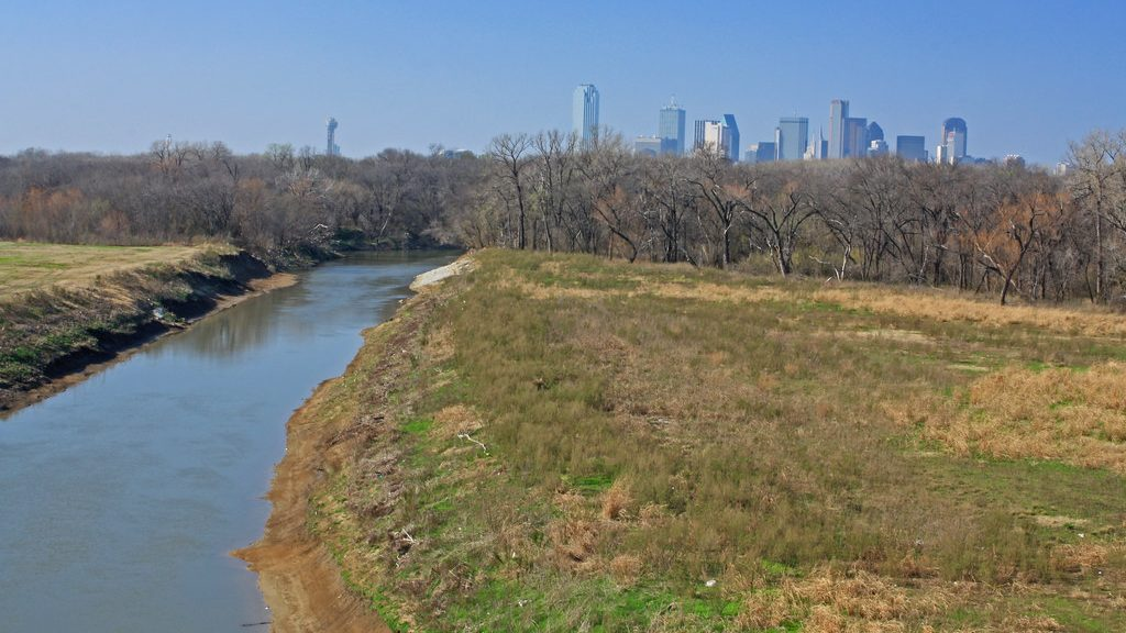 The Trinity River flows in the foreground and the Dallas, Texas skyline can be seen on the horizon.