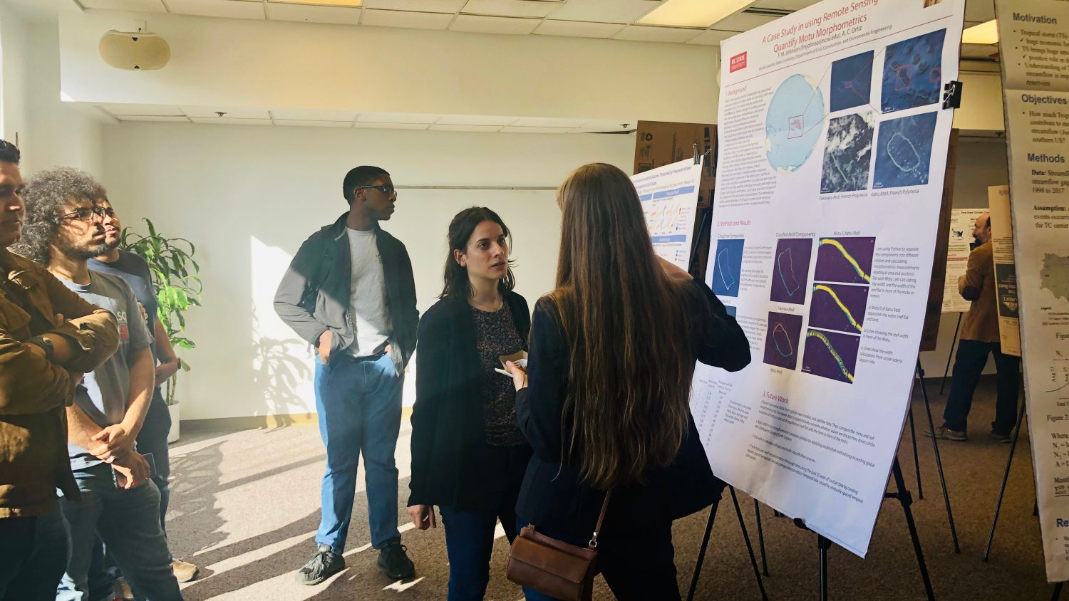 Students discuss a research poster at the RISING Poster Session.