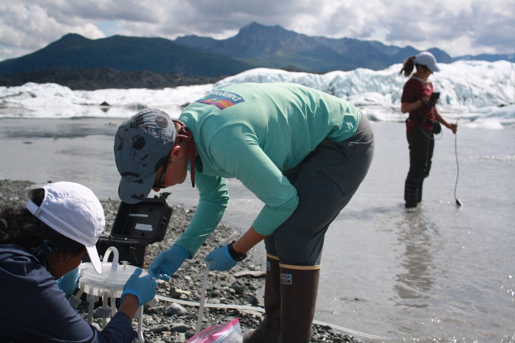 Global Change Fellow, Rachel Sussman, works with a lab-mate to conduct field research in Alaska. A beautiful, mountainous Arctic landscape stands above them in the background.