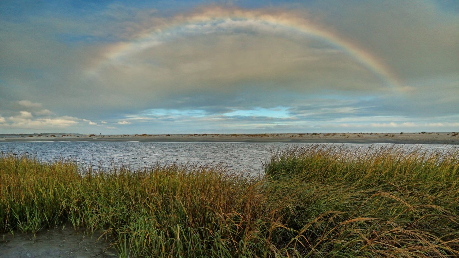 A rainbow sits above the horizon of the ocean at Saint Simons Island in Georgia