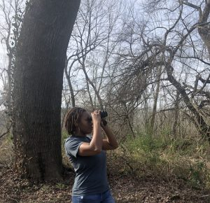 2018-19 Global Change Fellow and Graduate Student Intern, Deja Perkins peers through her binoculars toward a bird in the distance.