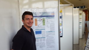 Adam Terando in front of row of science posters